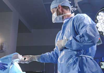 Dr. Brian newell is handed tools for a surgery.