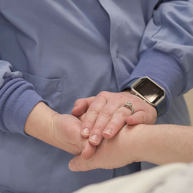 Provider and patient holding hands in a caring pose with Gritman General Surgeons